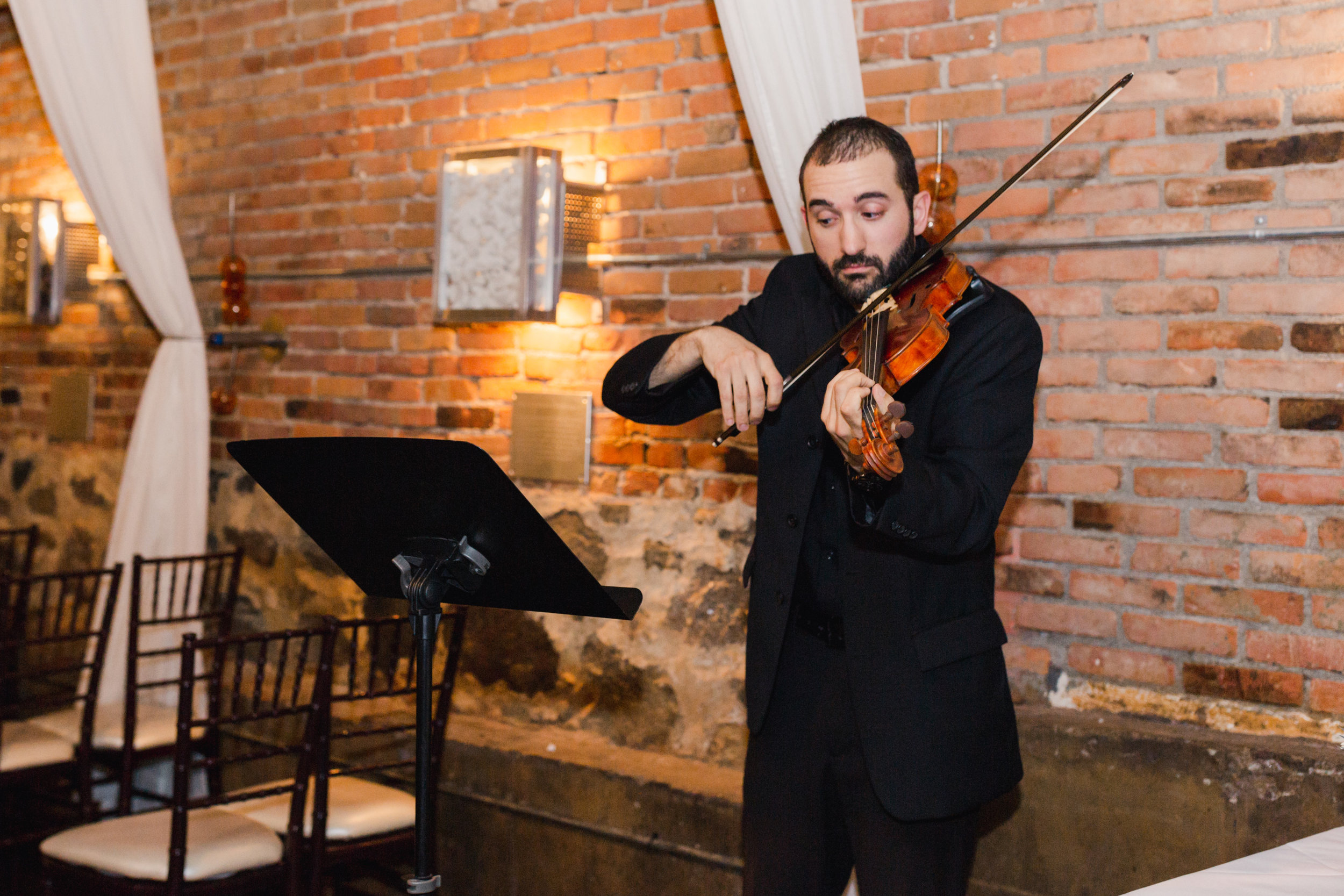 Solo Violinist Daniel Winnick performs for the wedding ceremony. Captured by  Stephanie Kaslly Photography.