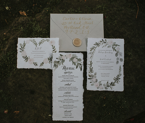 The Anne  The Anne features sweet soft pink and green florals and the most darling heart shaped wreath. Hand calligraphed names and envelope color of your choice round this beauty out.The Anne style starts at $225 for 100 invitation sets including the invitation, rsvp card and blank envelopes for both..