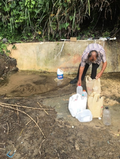 A man collects water after Hurricane Maria cuts water service to his home in Puerto Rico. Photo: David Harvey