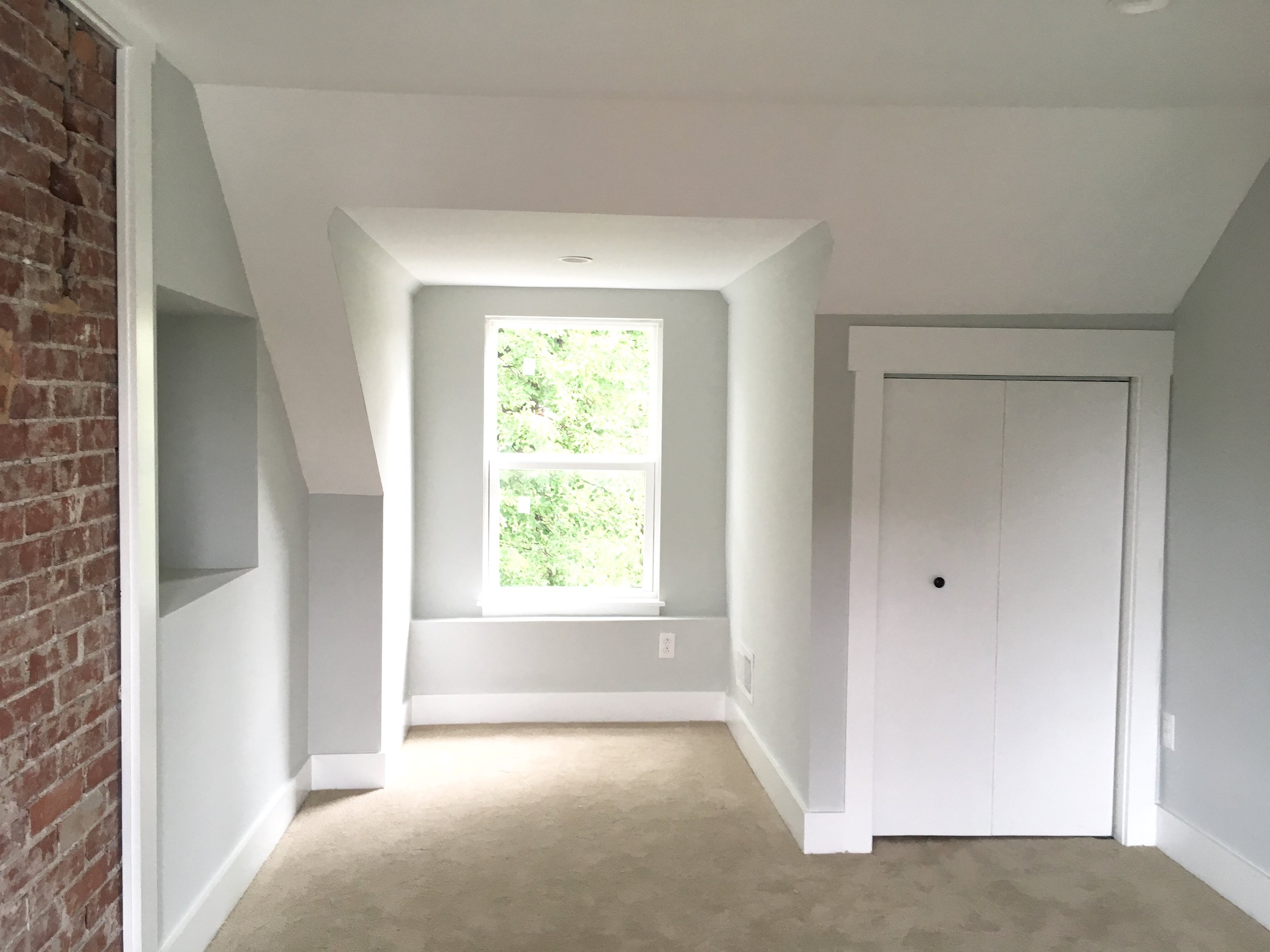 After: since this bedroom is awkwardly shaped, the wall was framed out flush on either side of the fireplace to provide a place for a bed. A new closet is tucked under the sloped ceiling line.