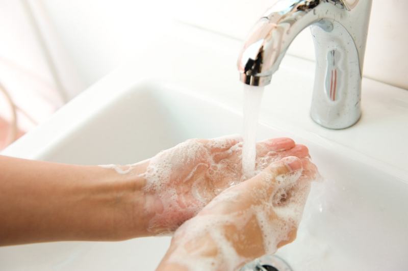 Someone washing their hands with warm soap and water