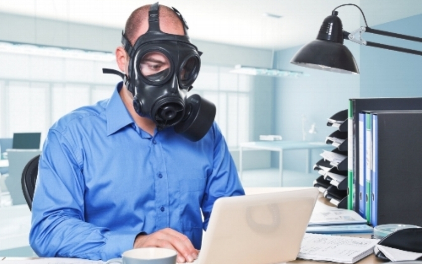 Man fighting air pollution by doing work with a gas mask on