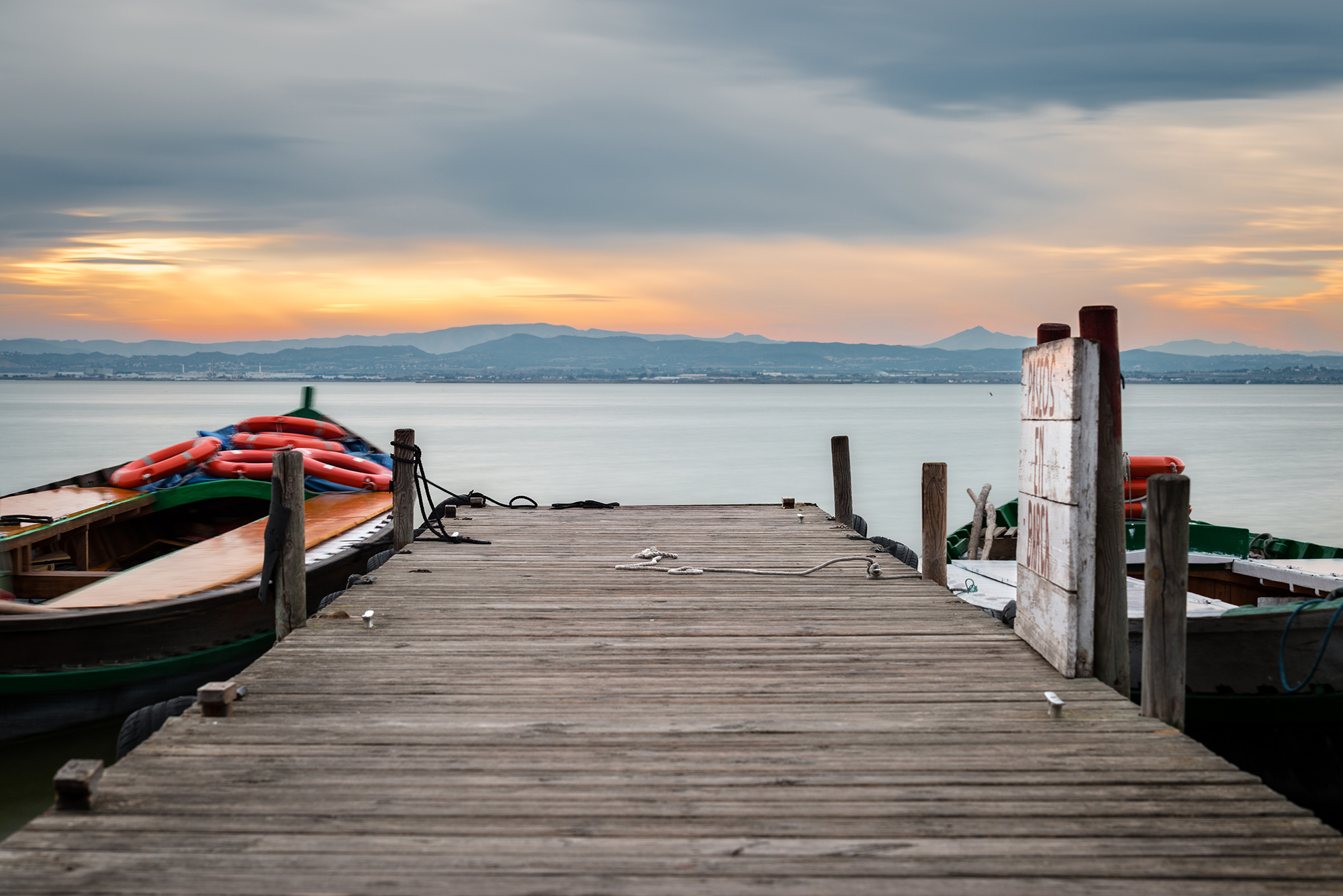 Jetty and small wooden boat at dusk in the Albufera in Valencia