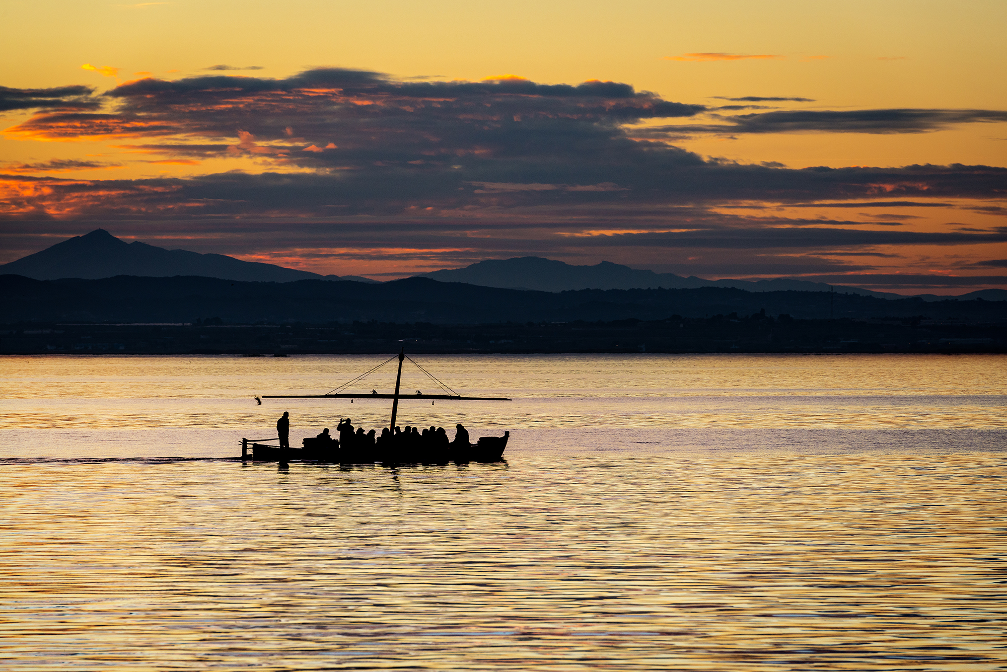 Silhouette of a small traditional boat at dusk in the Albufera in Valencia