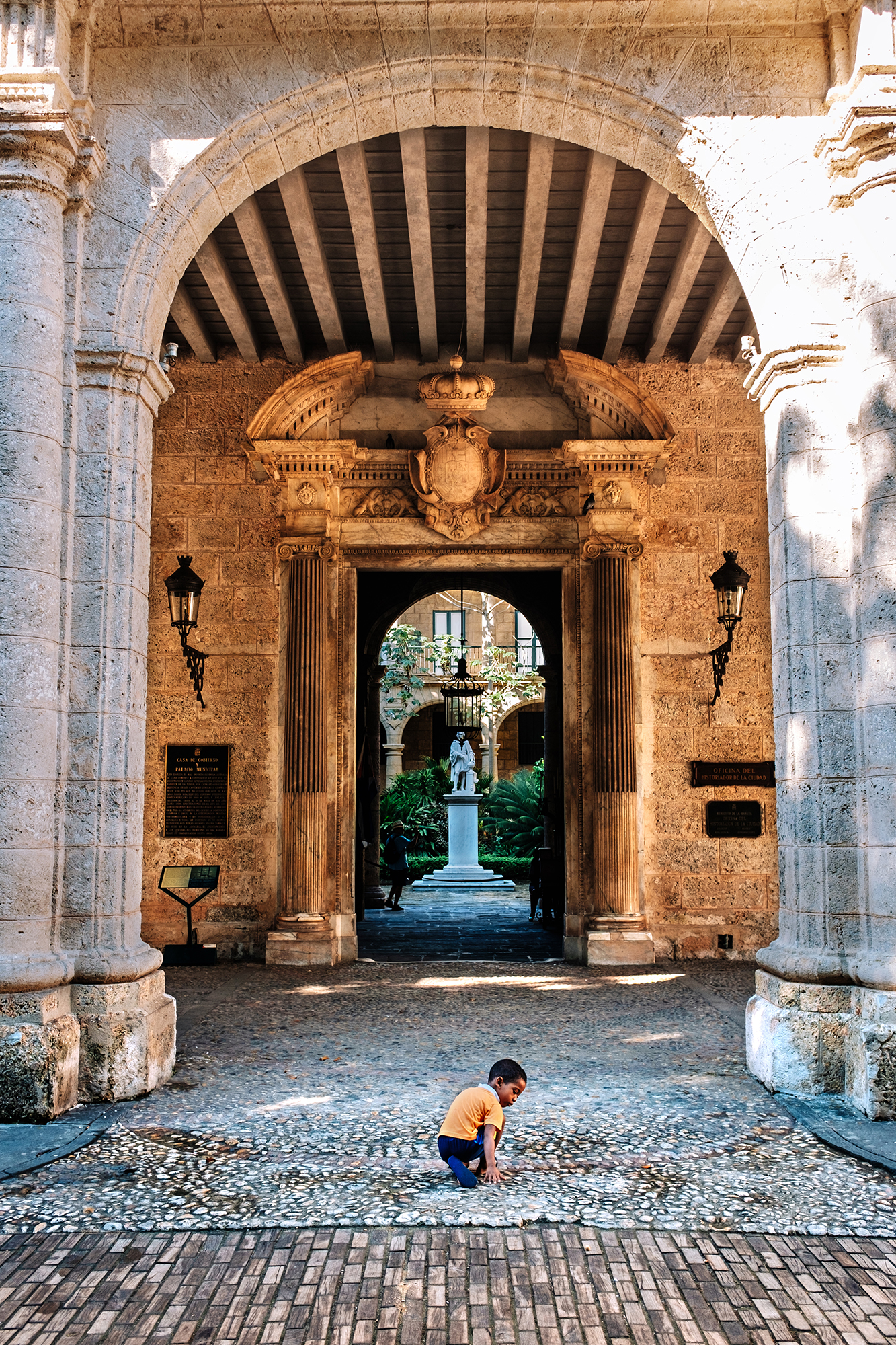 Young kid playing on the floor at the entrance to the Palacio de los Capitanes Generales