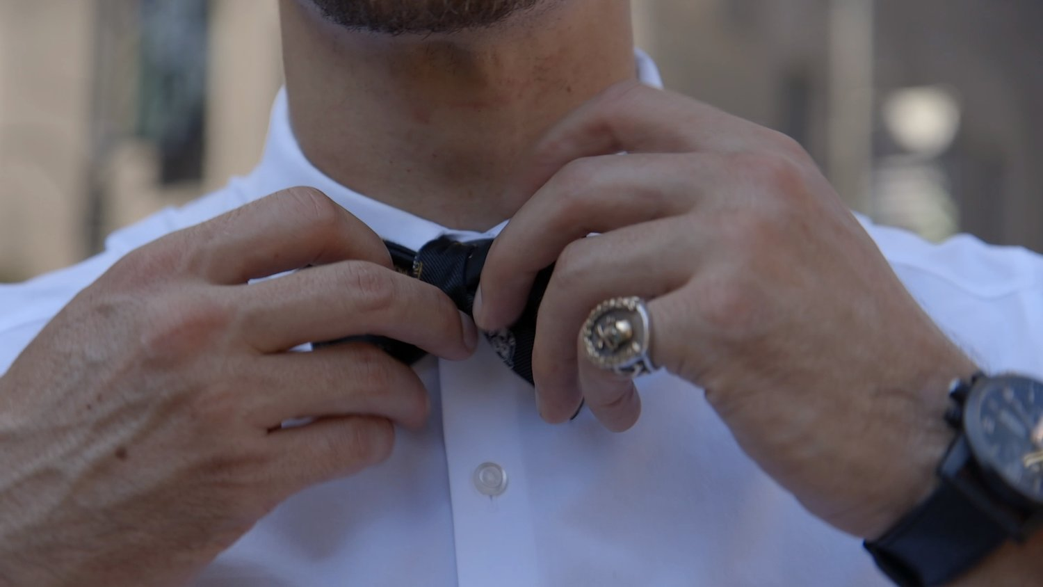 MAN ADJUSTING BOWTIE