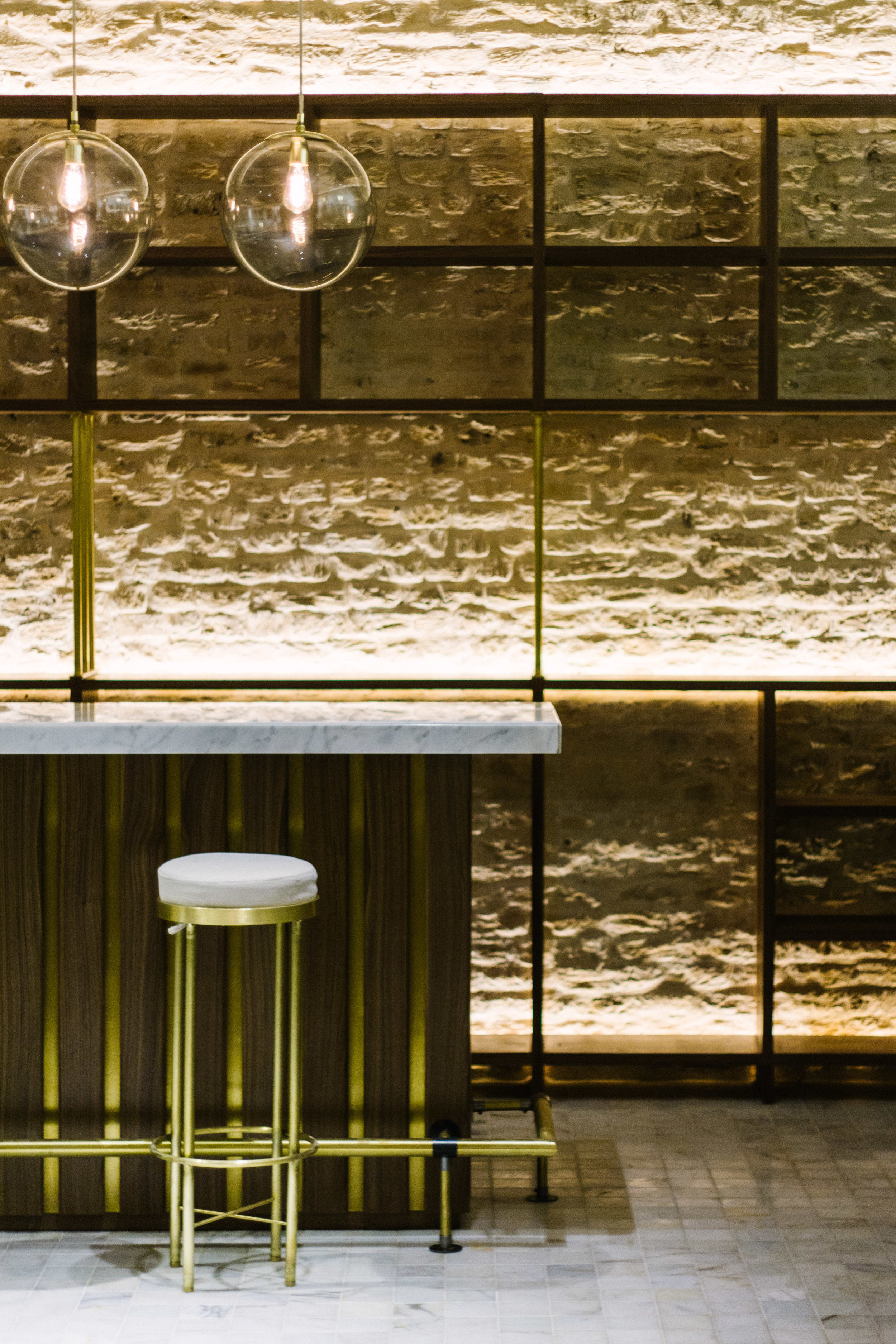 The bar was crafted in walnut wood with bronze accents and a marble tabletop, photo by  Santiago Marzola .