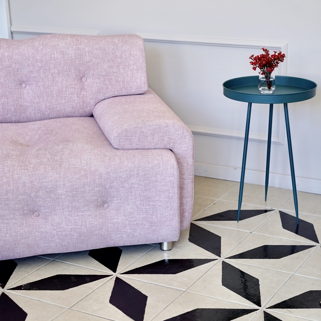 In the garden room.... - ...we especially love the pink armchair and black and white mosaic floor tiles.