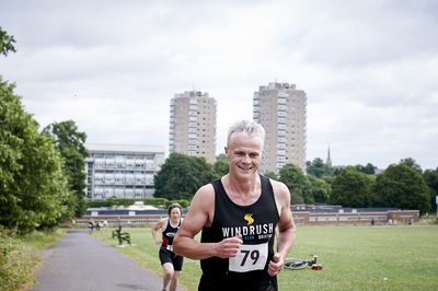 Male competitor wearing aquathlon t-shirt running in Brockwell park
