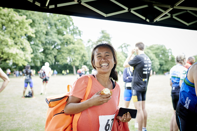 Smiling female competitor enjoying a piece of cake after aquathlon