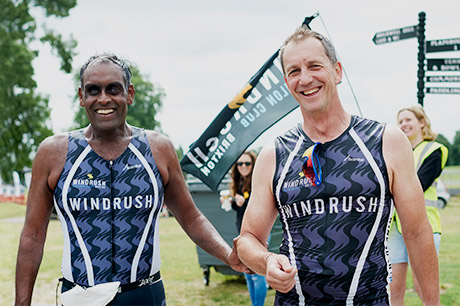 Two male Windrush athletes wearing race kit at Windrush Aquathlon. Windrush flag flying in background.