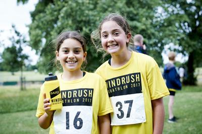 Two smiling girls in the park wearing yellow windrush aquathlon tshirts