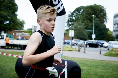Boy running across the finishing line