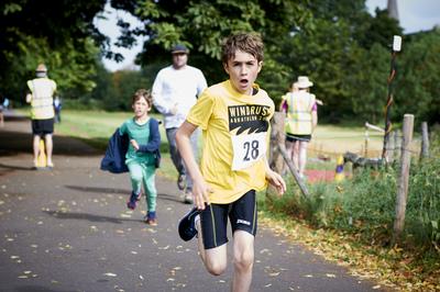Boy wearing aquathlon tshirt running in Brockwell park