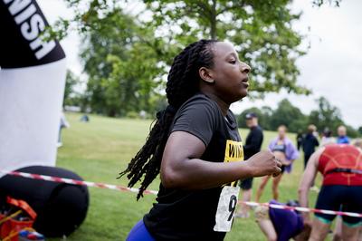 Female competitor running across the finish line at Windrush Aquathlon