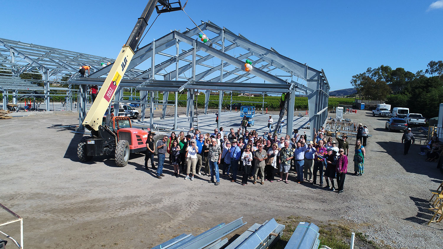 Roche Customers and Family toasting the placement of the last structural member placed for the new Roche Winery