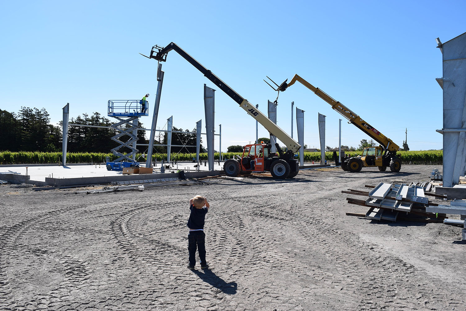 Liam Roche, son of Brendan Roche, looks on in awe of the big machinery used to set the framing in place