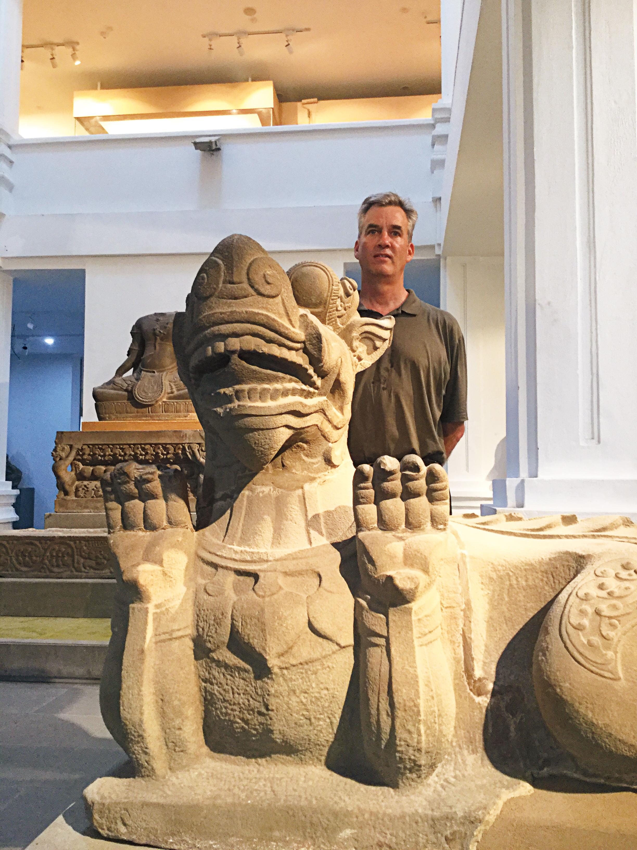 Scott Elder '78 in Vietnam with a Champa Kingdom sculpture.