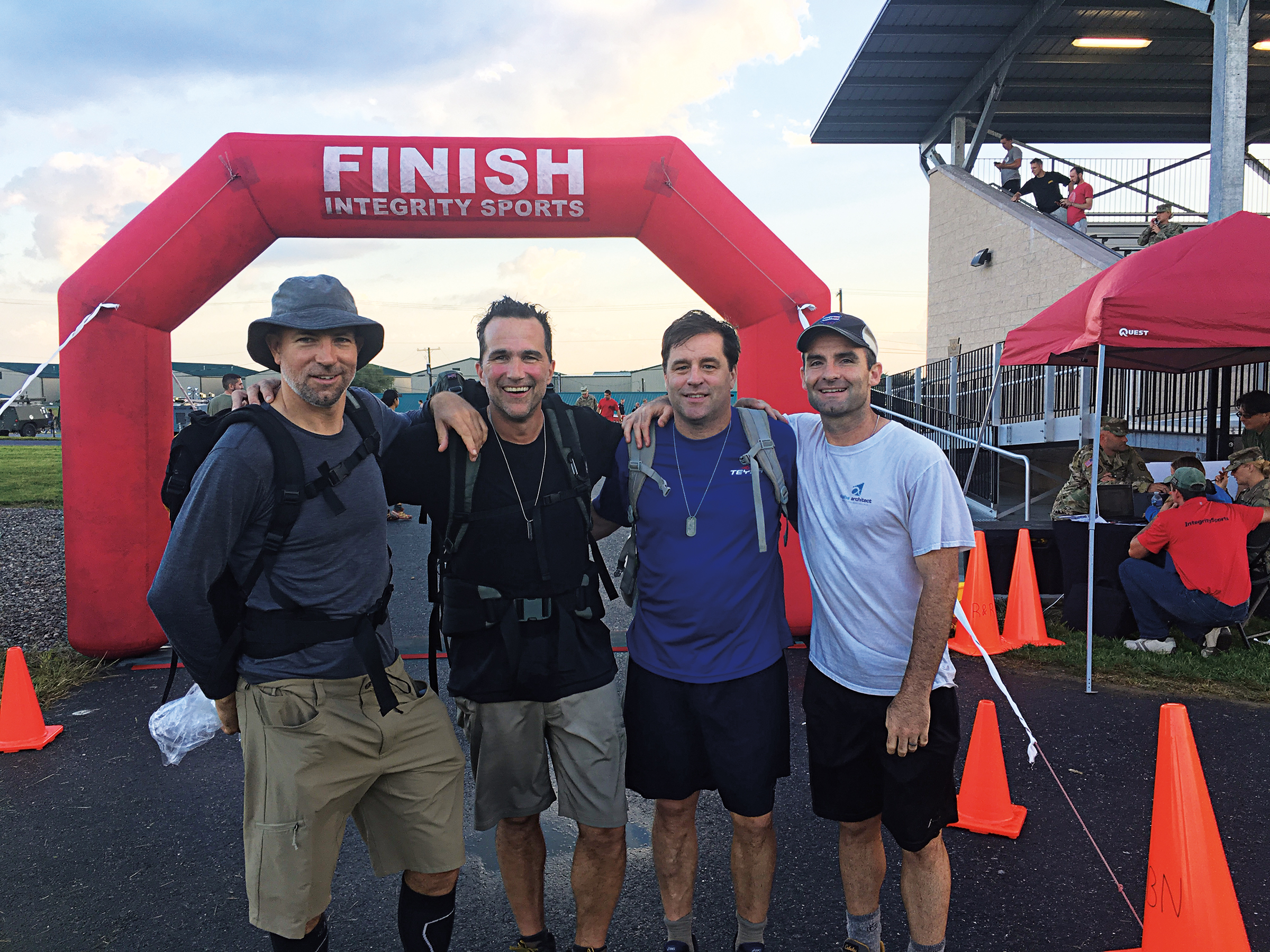 (L. to r.) Bart Quillen '85, Charlie Shaffer '85, David Foulke '85, and Capt. Wes Gray at the finish line after the 28-mile March for the Fallen.