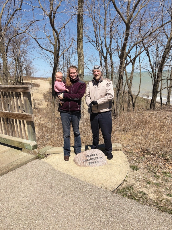 J.T. Howell '72 with his daughter, Lizzy, and granddaughter, Loria, standing by a memorial for formmate Harry Chandler in Highwood, Ill.