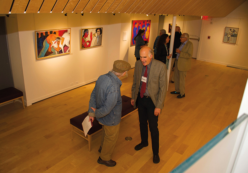 Former faculty member Charles Lemeland (l.) with Kedron Barret '79 in front of paintings by Kedron's mother, Leni Mancuso Barrett.