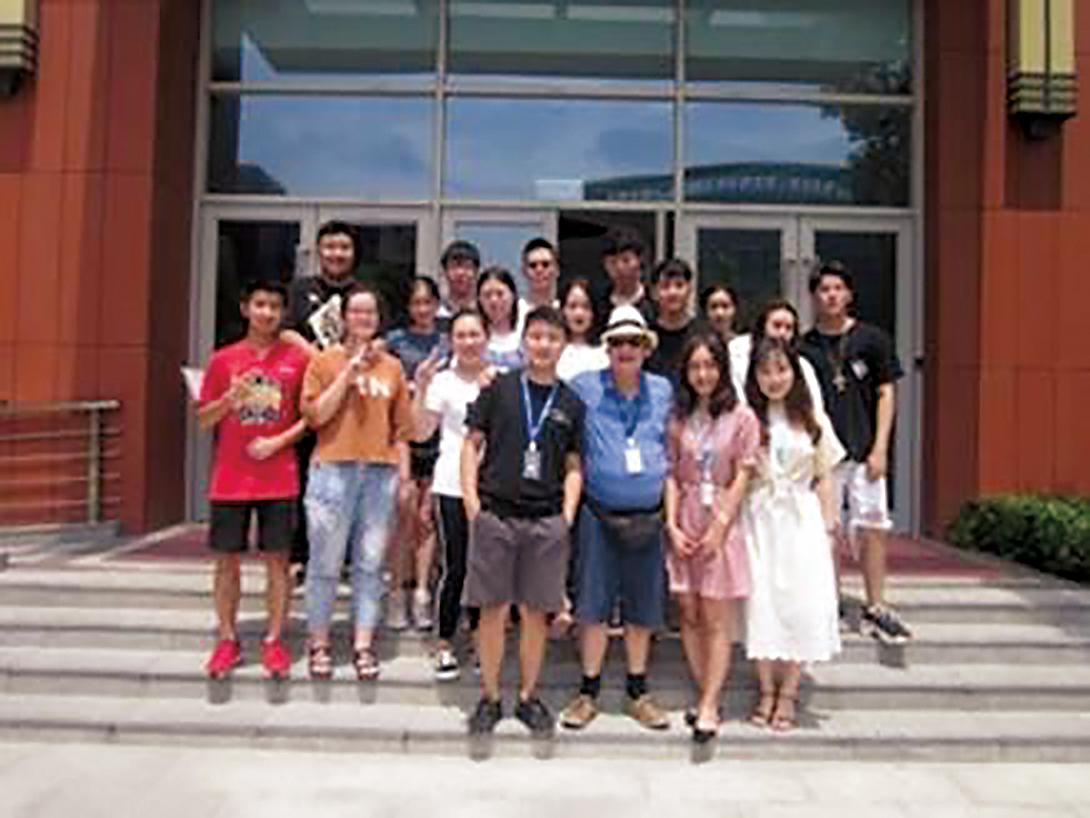 Lin Giralt '72 (blue shirt and hat) with his summer school class at Shanghai's Jiao Tong University.