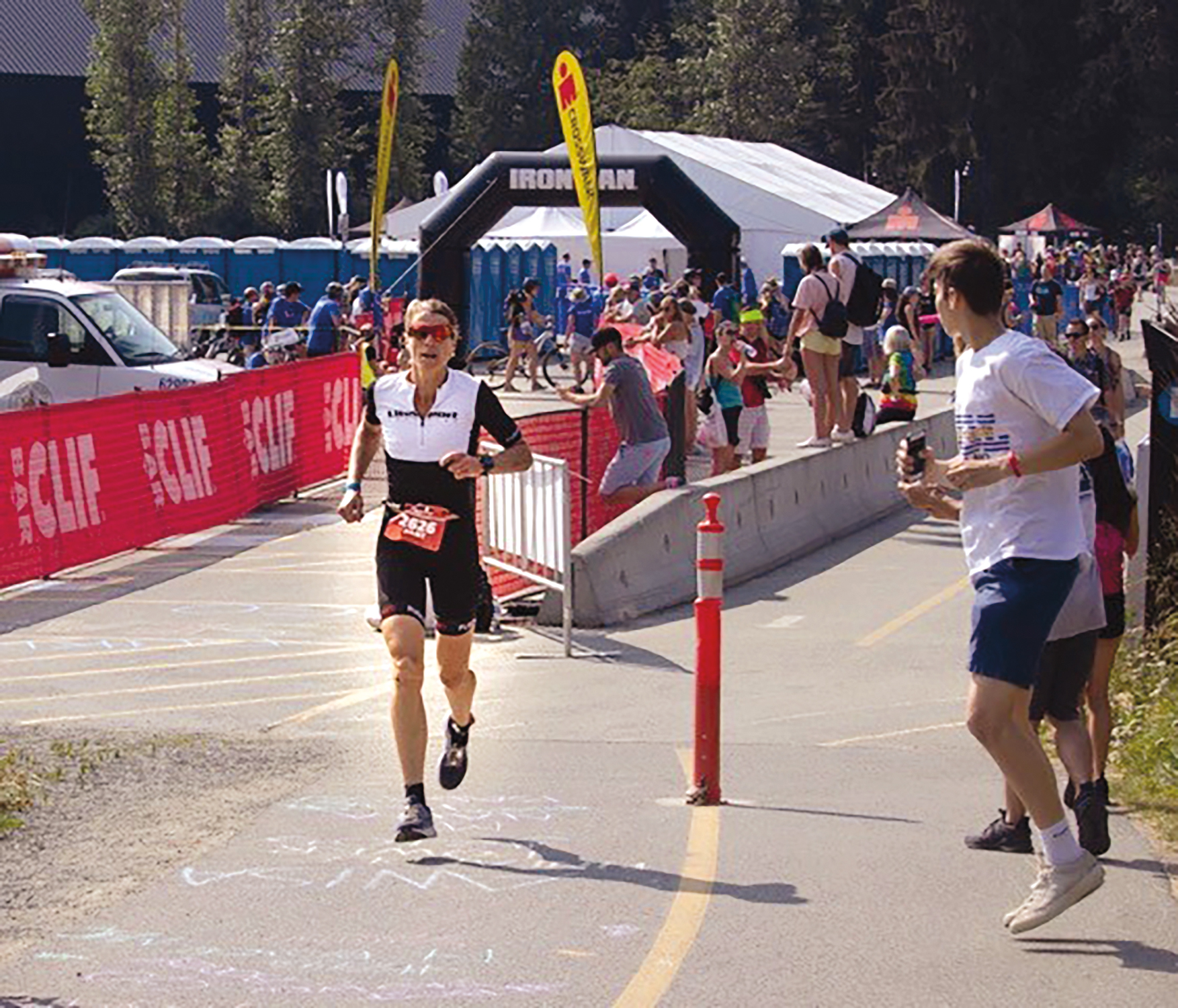 Juliet Hochman '85 competing in the half-Ironman triathlon in Whistler, B.C., and receiving real-time race intel from son Thomas.