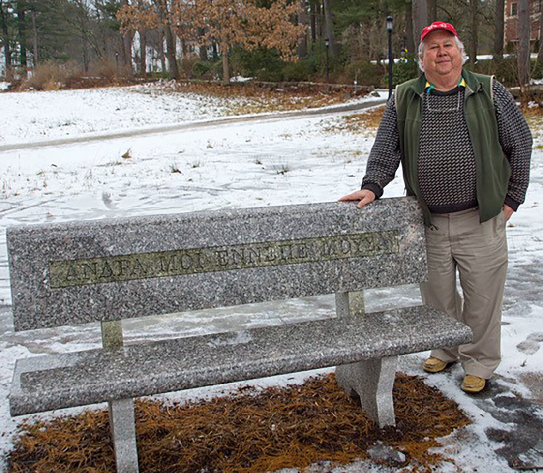 Bert Myer '62 standing by the Ellerbe Cole '62 memorial bench at SPS.