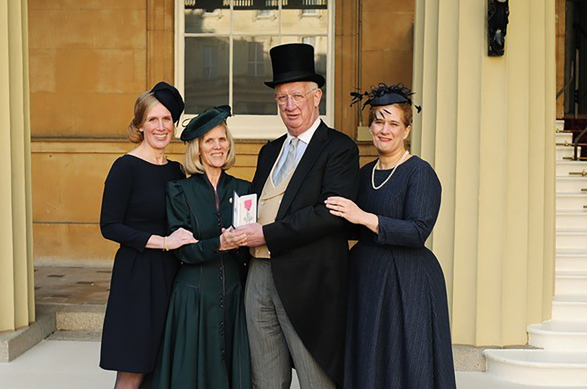 Laura Hildesley Bartsch '86 (l.) at Buckingham Palace, where her father, C. Hugh Hildesley, P'86, GP'14,'17, was invested as a Member of the Order of the British Empire by Prince William.