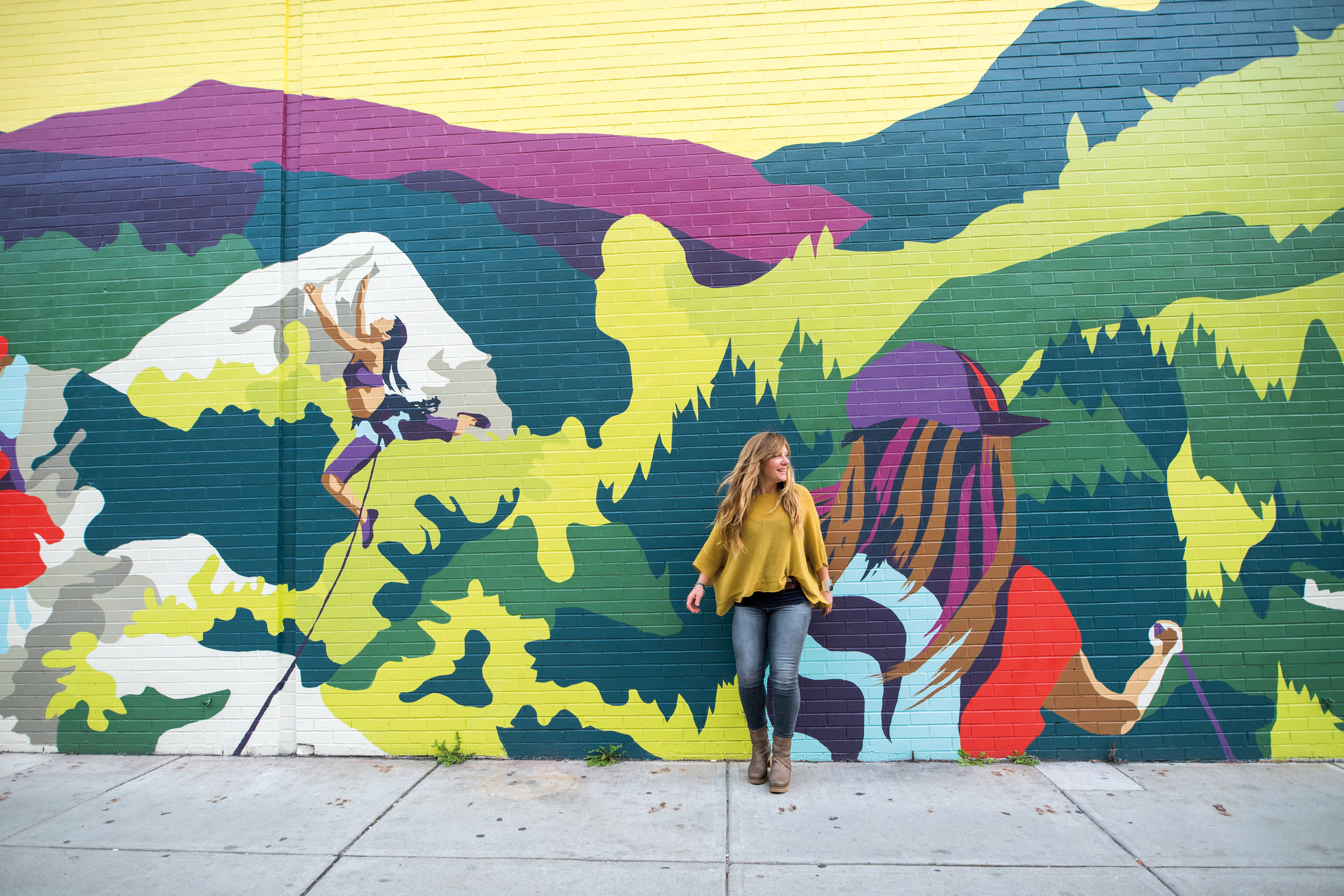 "Jess Graham '95 in front of her ""Our Mountains, Our Home"" mural in Burlington, Vt."