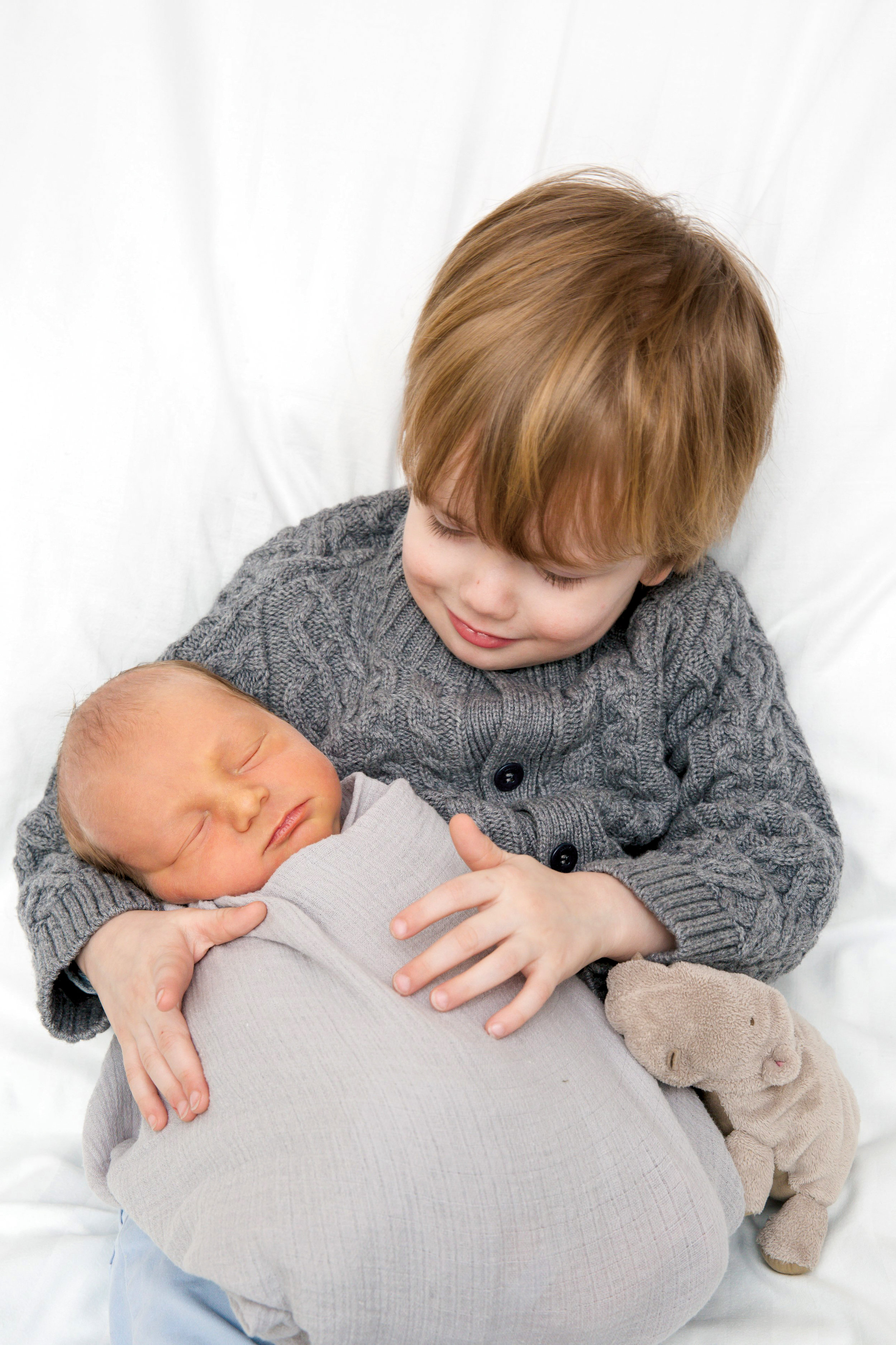 Baby Theo, son of Megan and Adam Brandow '99, being held by his big brother, Otto.