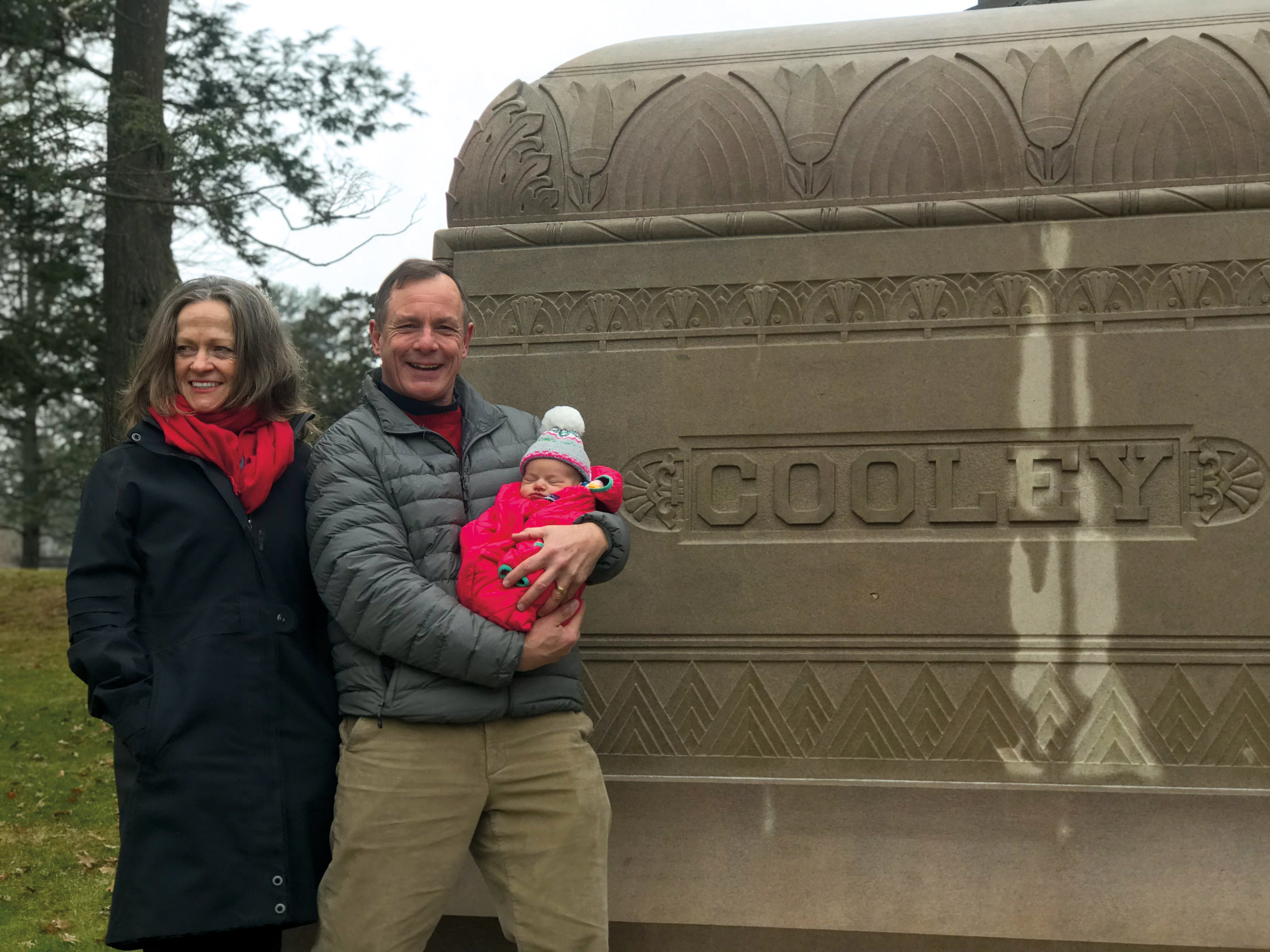 Jeff Cooley '75, with wife Betsy, holding his granddaughter, Claire (daughter of Ben Cooley '03), in front of the resting place of Jeff's father, Paul Cooley (Form of 1926).