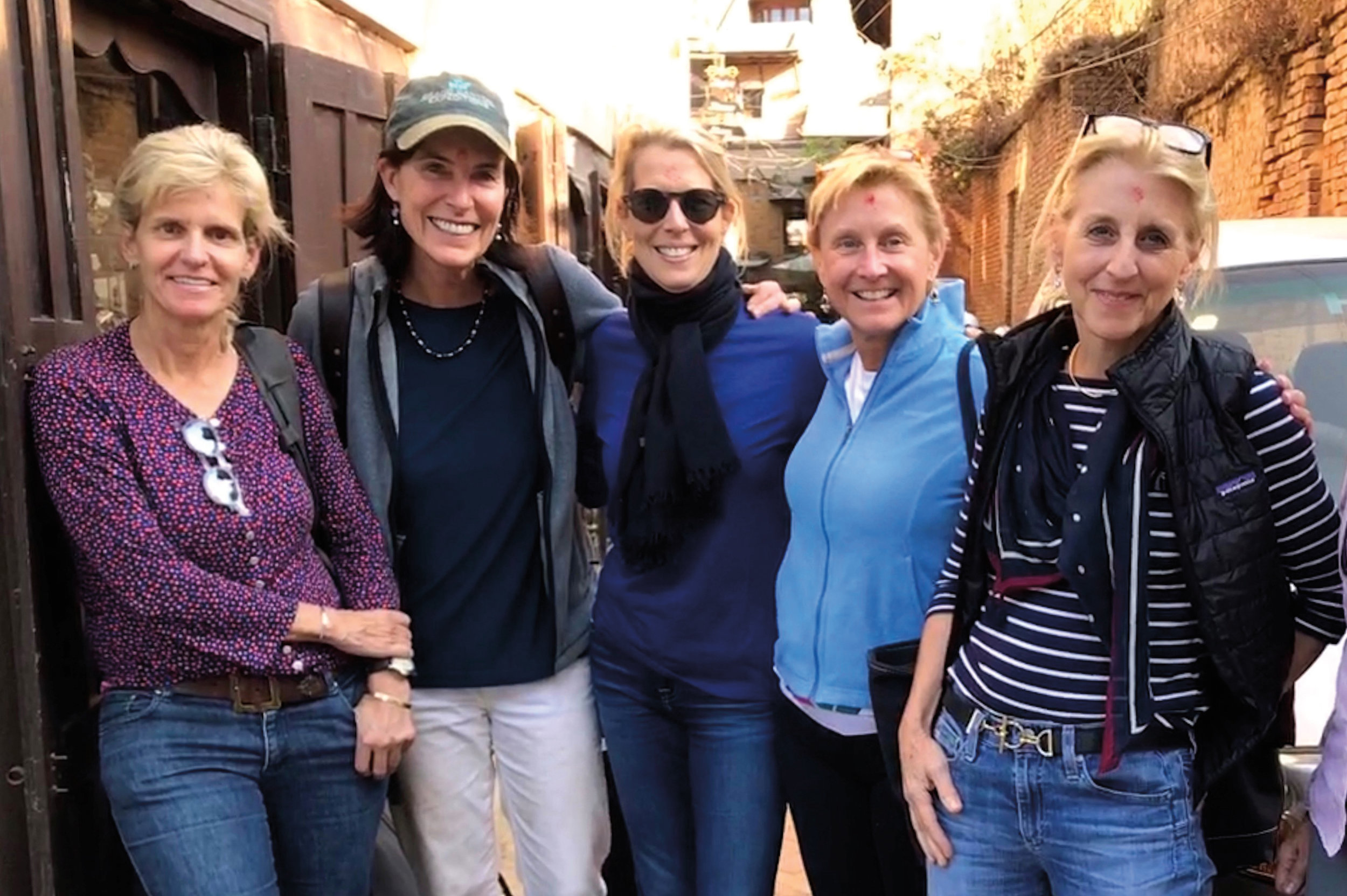 Lisa Kent Nitze '78, Lisa Henriques Hughes '78, and Electra McDowell Lang '78 (c.), flanked by two of their fellow trekkers in Kathmandu, Nepal.