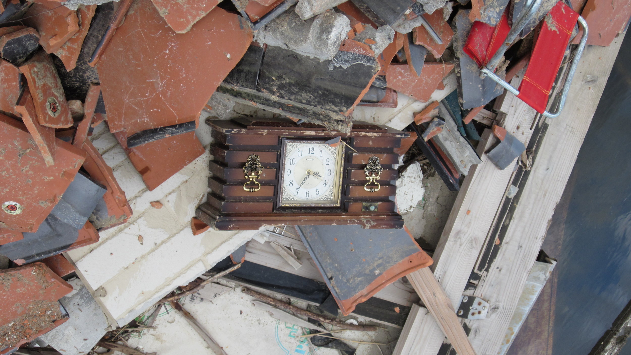 A clock rests amidst debris - the time reads 3:35, likely the time at which it was submerged by the tsunami