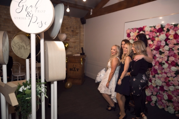 A photo booth and flower wall in action. Image credit:  White Locket Boutique Photography
