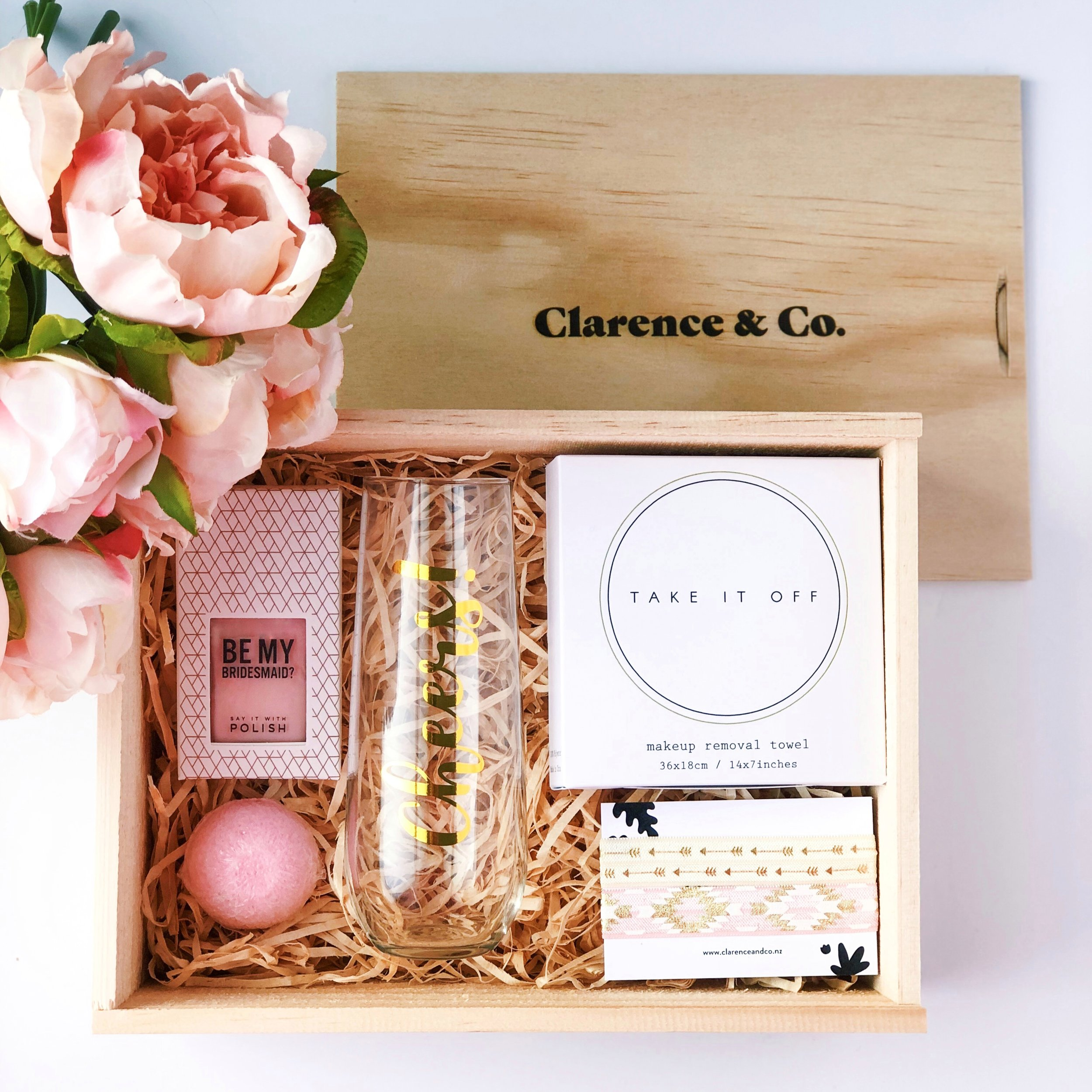 """Clarence & Co. Box   Beautifully packaged in our New Zealand-made pine plywood gift boxes and wrapped with ribbon. We love that these boxes can be reused for a lifetime.   Set of two assorted """"to have and to hold"""" hair ties   These bridesmaid themed hair ties are an extra cute addition when asking your besties to help you """"tie the knot"""".   Light blue or pink bath bomb   Lovingly hand-crafted in NZ, these bath bombs are cruelty free and all-natural. Pamper time before the wedding is a must!"""