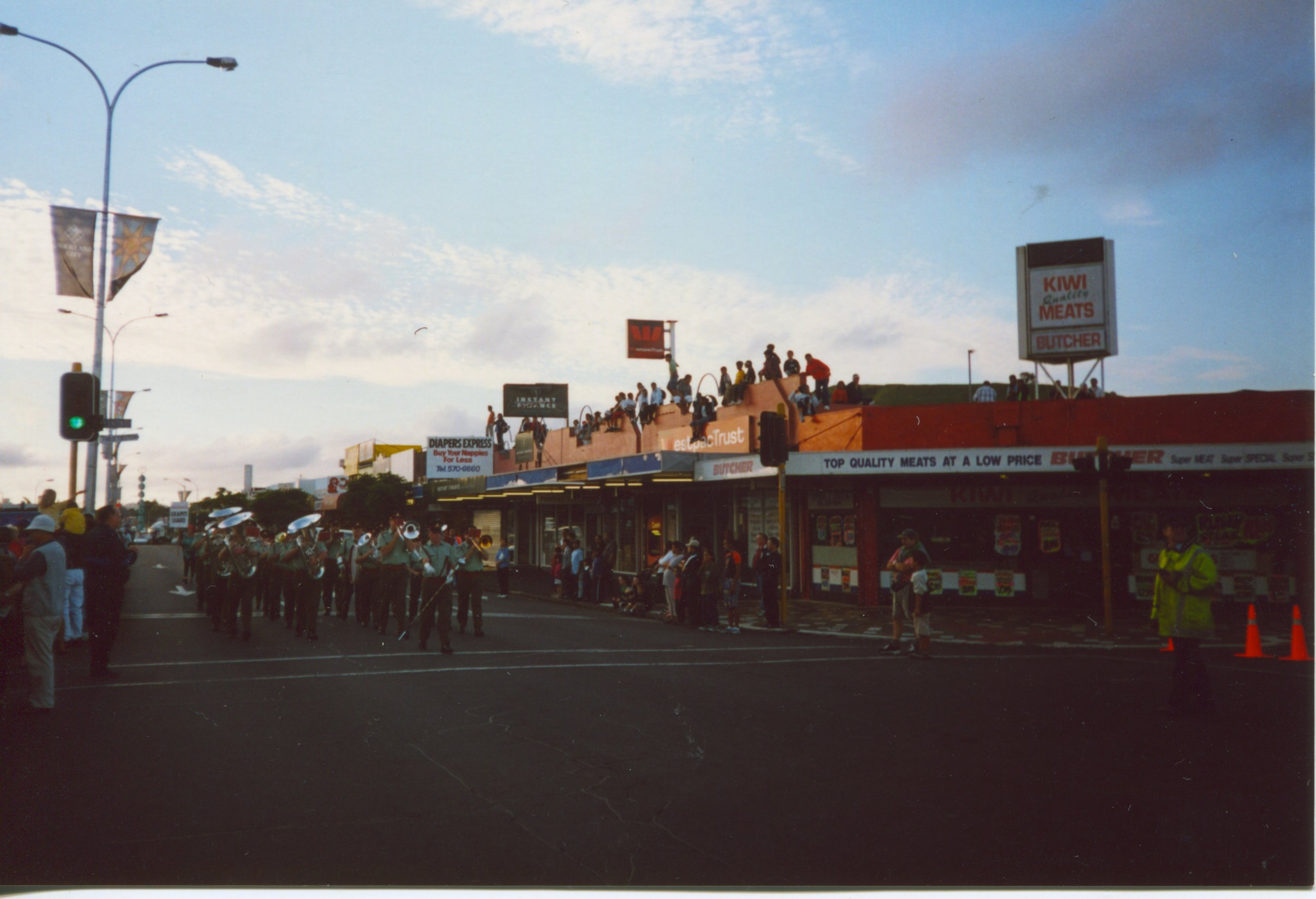 Crowds sit on the shop roofs to watch the Santa Parade. Date unknown. Image courtesy of the Panmure Historical Society.