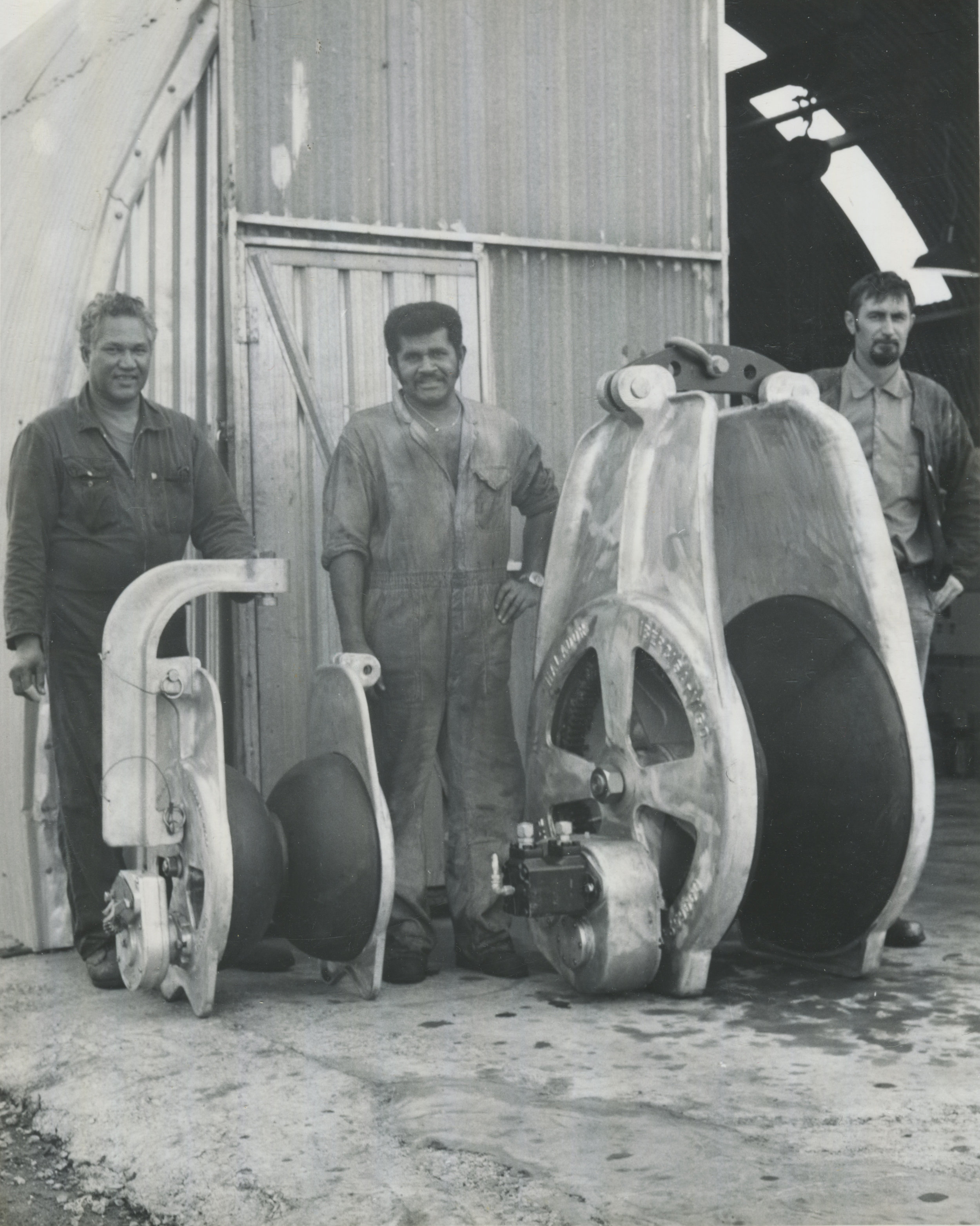 """The dock workers (Jack O'Brian, unknown and """"John the Pom"""") standing with their ship pulleys in 1970s. Courtesy of Titan Engineering."""