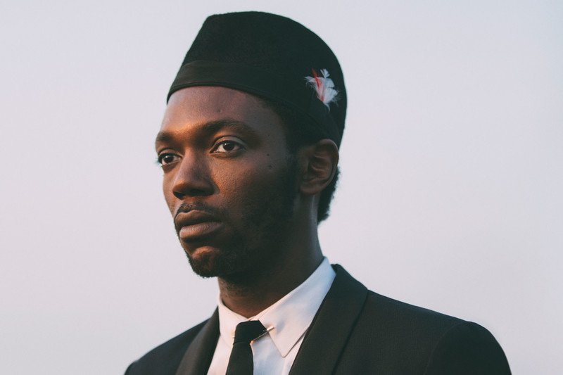 """BALOJI - Baloji is a poet, composer- lyricist, scriptwriter, actor and performer, video artist and stylist. After the release of his album Hotel Impala (2008), his Congolese reinterpretation (Kinshasa Succursale, 2011) was awarded 4 stars by the world's press (NYT, Guardian, El Pais, Les Inrocks..) and after more than 200 live shows all over the world, Baloji is back with a new EP. His music stands at the crossroads of African music, traditional and afro- american music (soul, funk, jazz) discovered through the culture of sampling and electronic music (trance, deep house) which has its roots in part in the region of Belgium where Baloji grew up. Baloji means """"man of science"""" in Swahili, but during the colonial period that meaning shifted to """"man of the occult sciences and sorcery"""". By placing his resilience at the centre of his work Baloji reconciles all these influences to enrich his projects."""