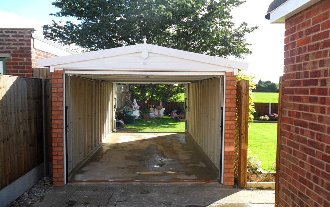 This garage has a retractable up and over garage door at both the front and the back so that a vehicle can be driven all the way through.
