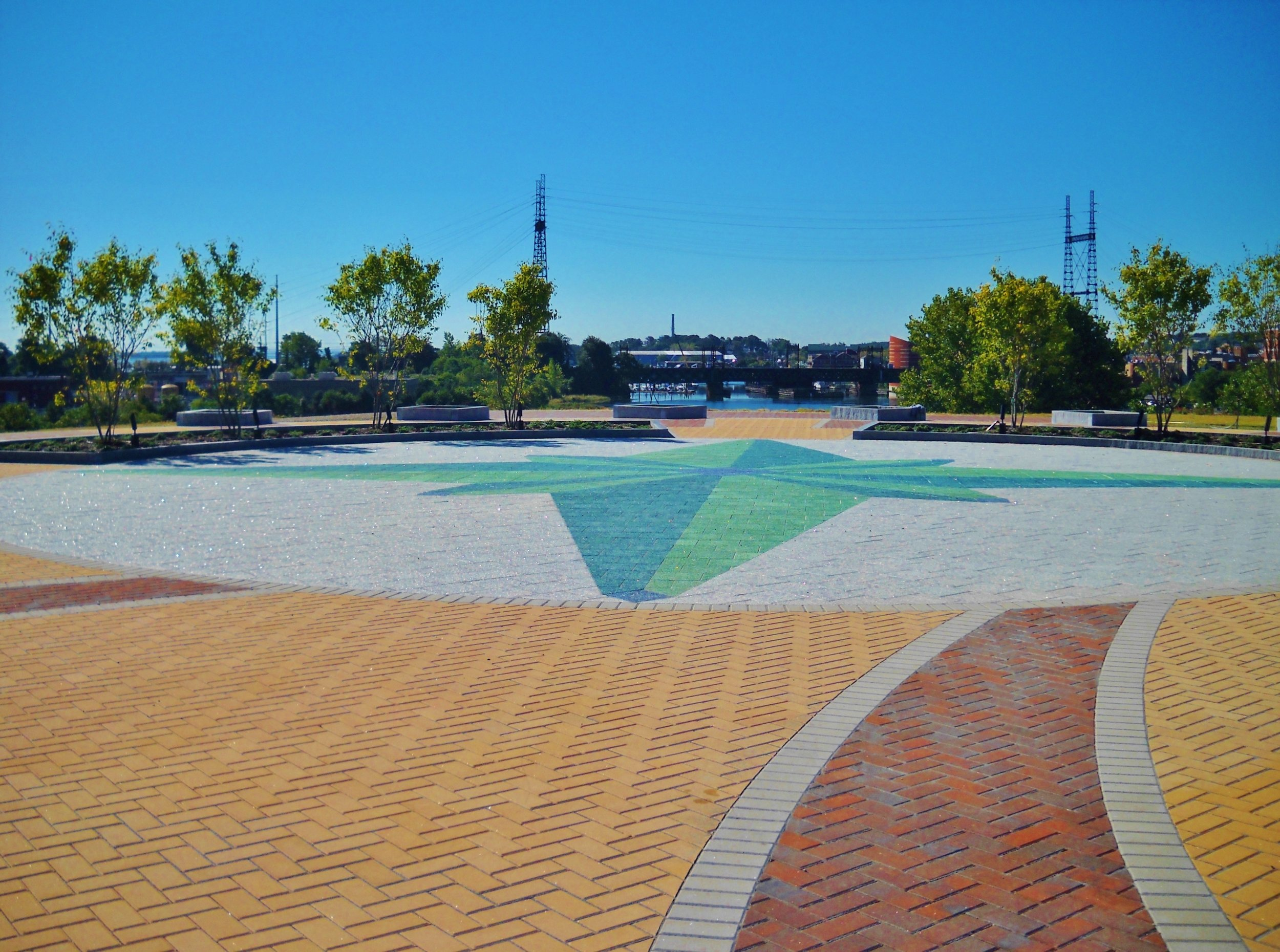 Paver installation featuring a blend of concrete pavers mixed with teal and blue recycled glass pavers