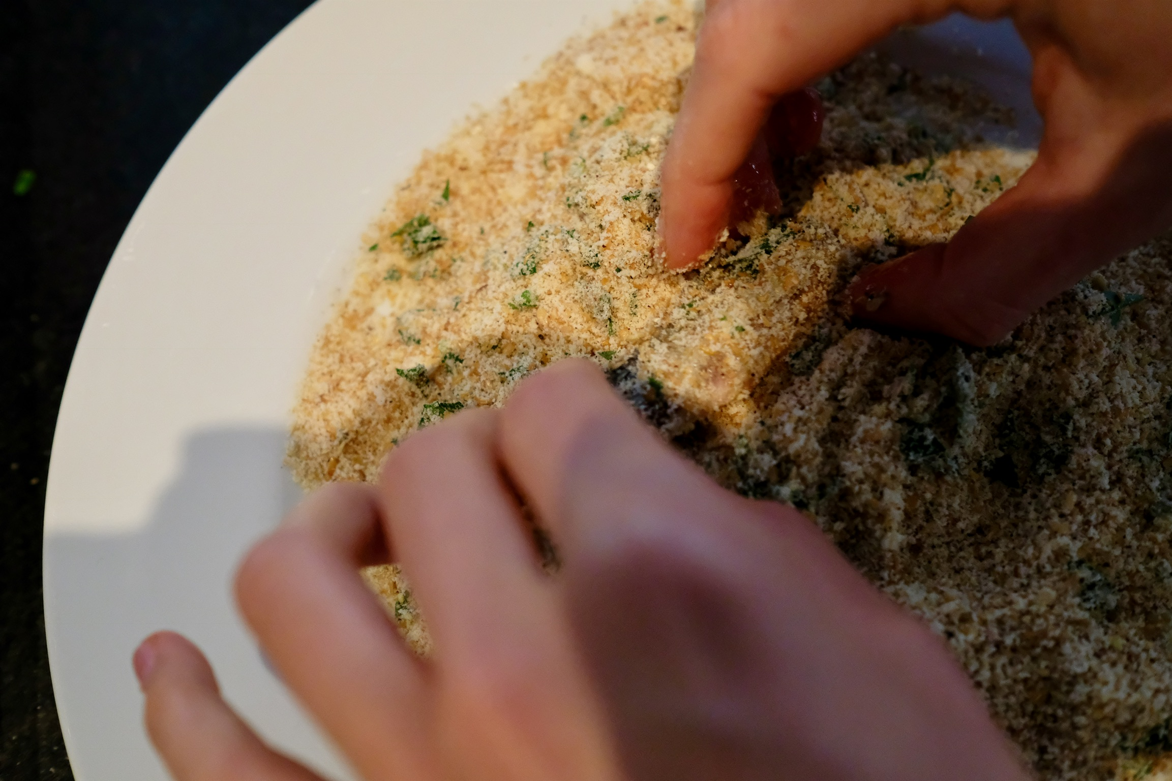 Coating the egg-covered sardine in the breadcrumb mixture