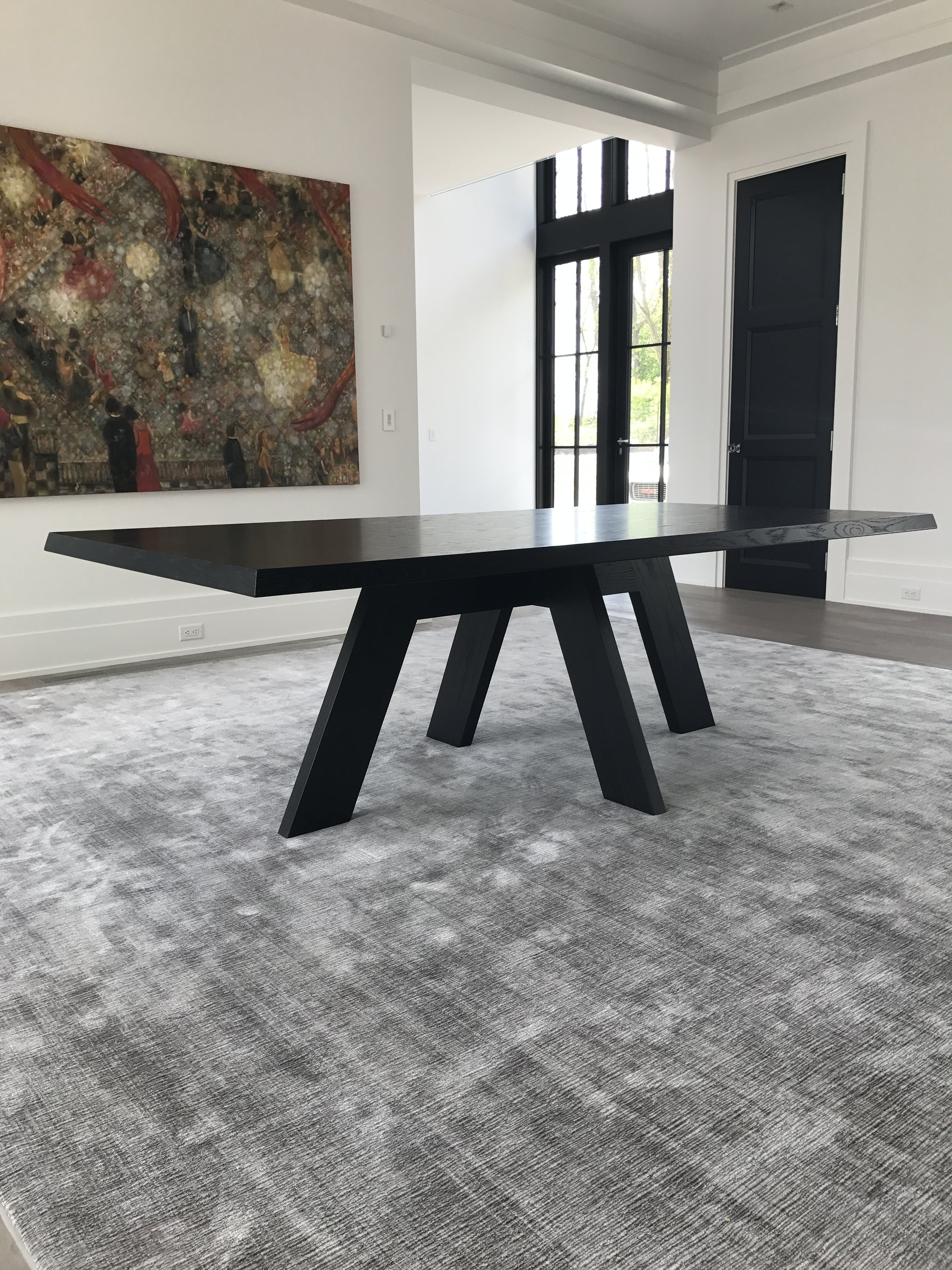 A rectilinear, ebonized white oak dining table.