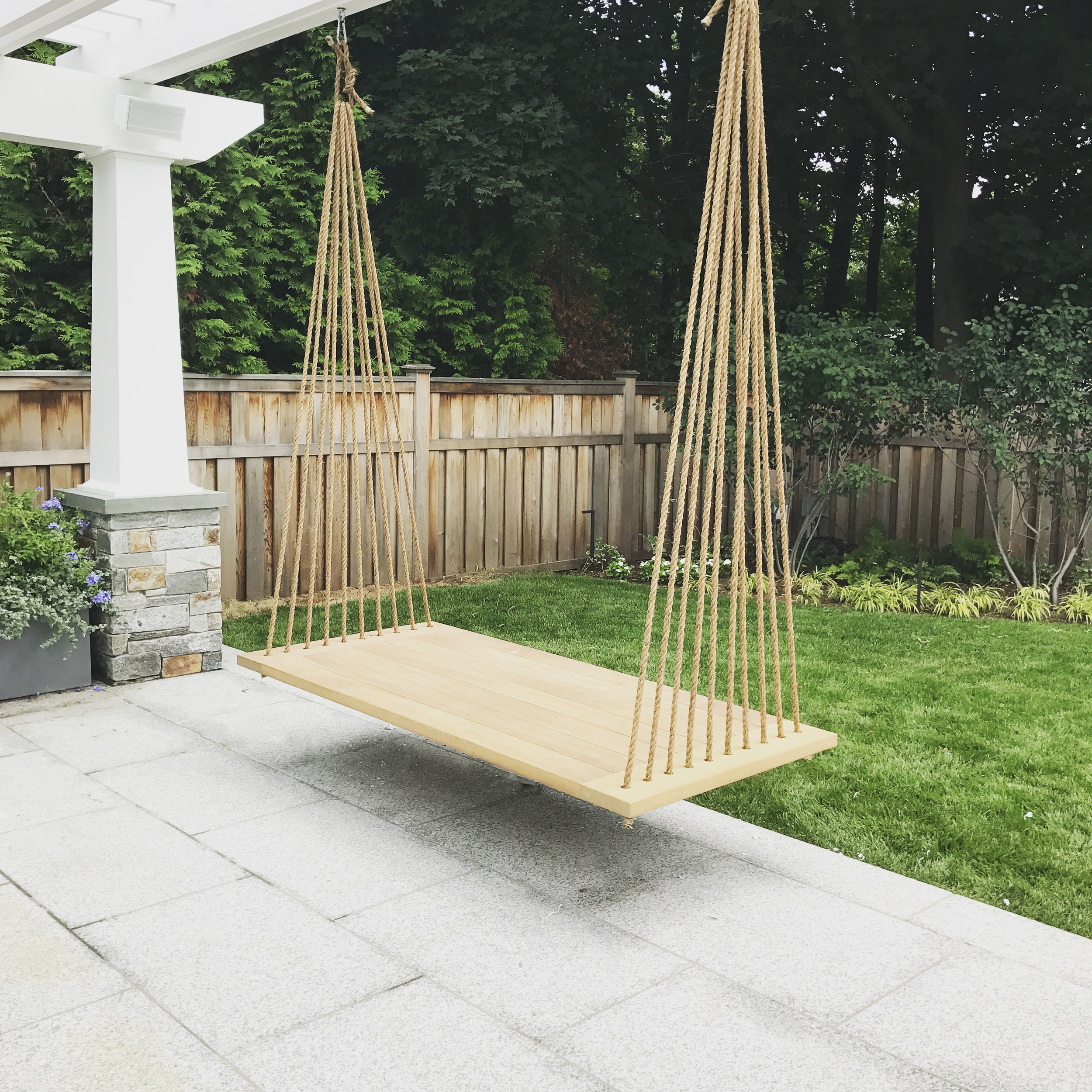 An outdoor swinging bed made out of Iroko Wood.