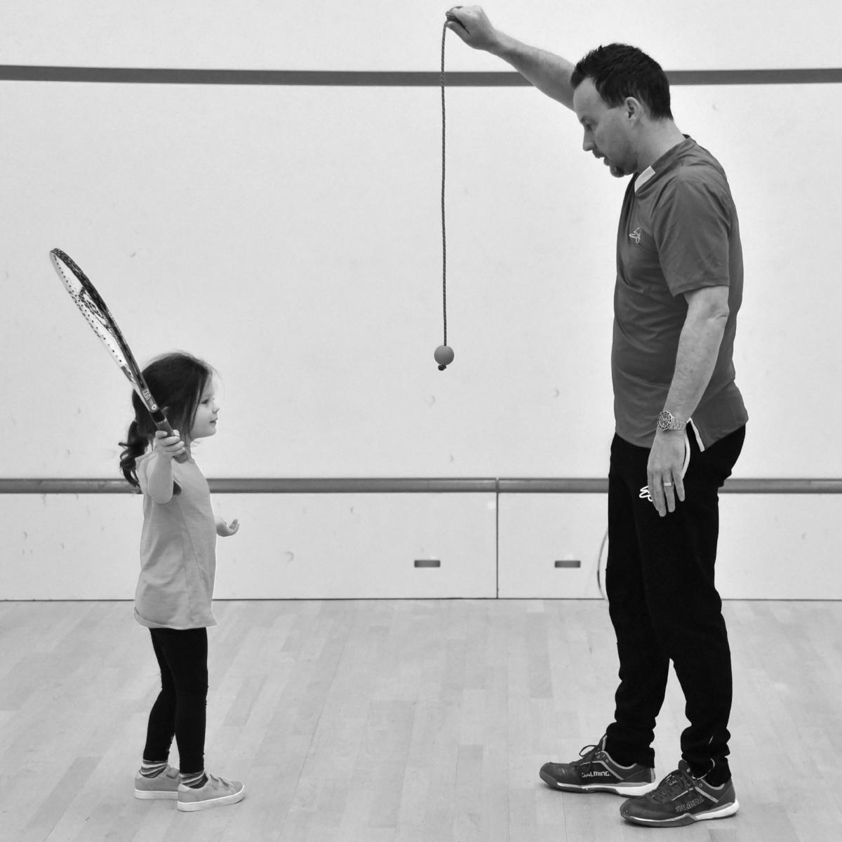 Junior squash player practicing swings with a practice squash ball
