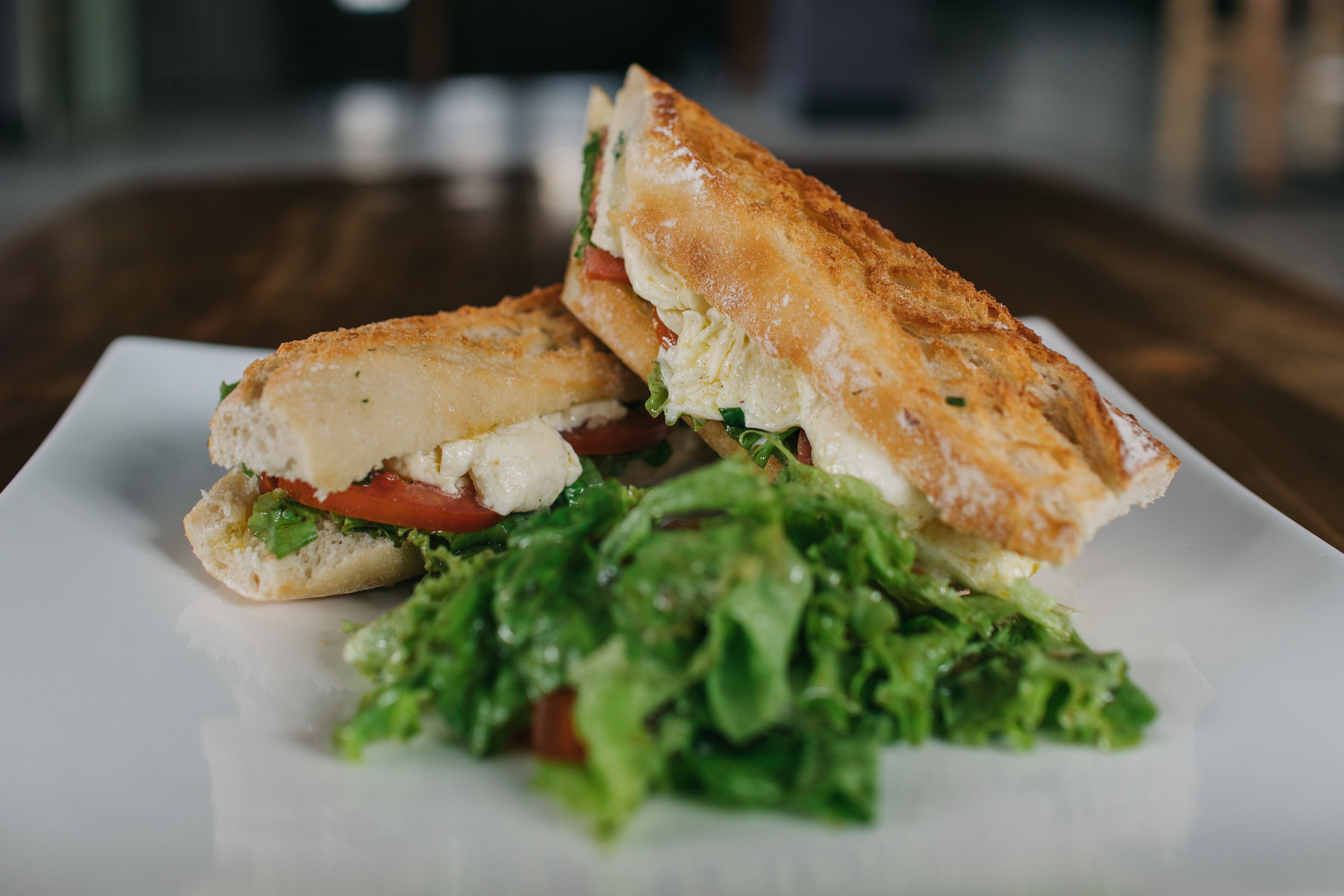 Lunch: : Sandwiches + Wraps come with a small house salad or fresh chips. - Featuring Tomato Mozzarella Sandwich with salad.