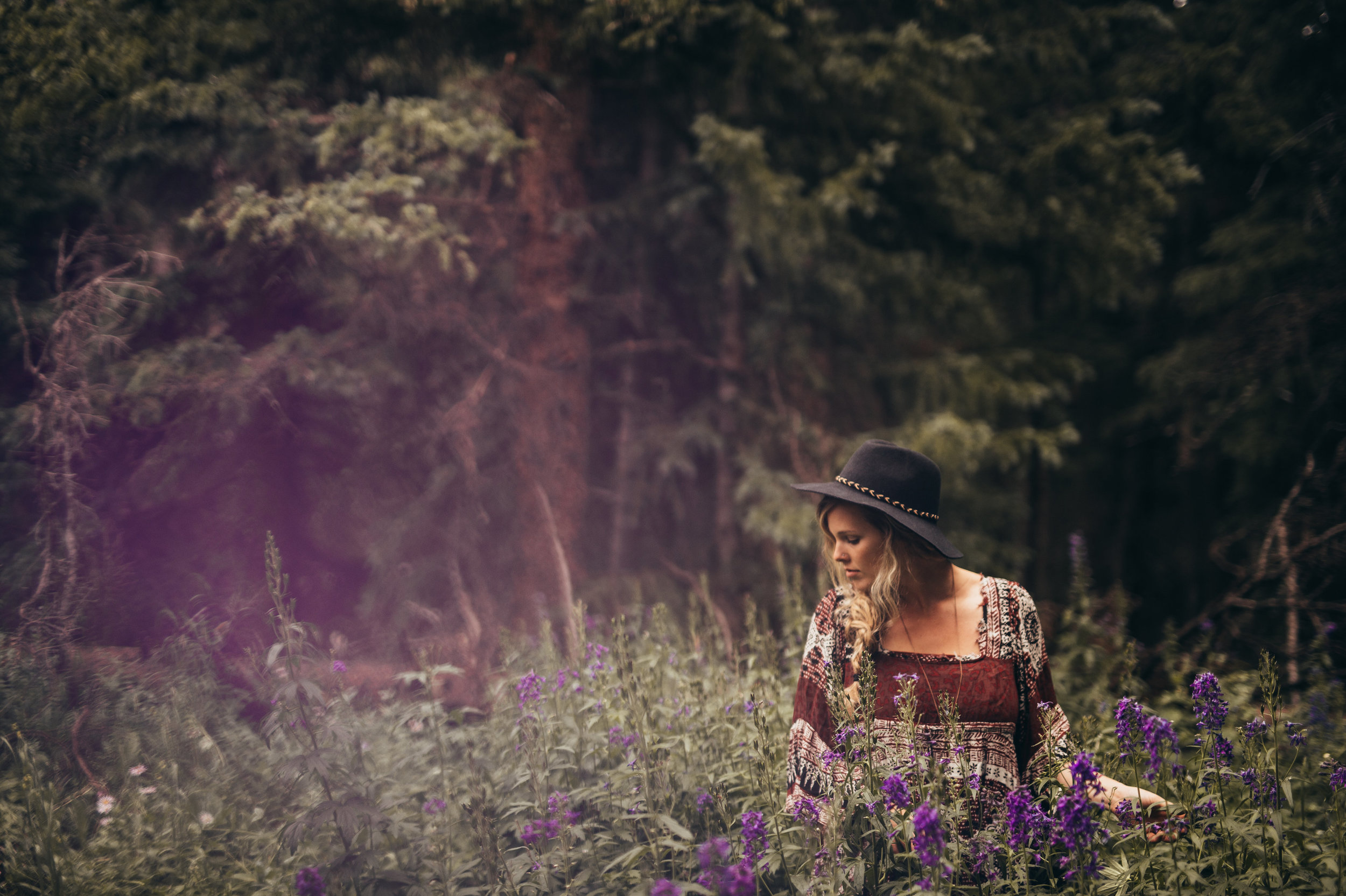 Woman with black hat in high grass