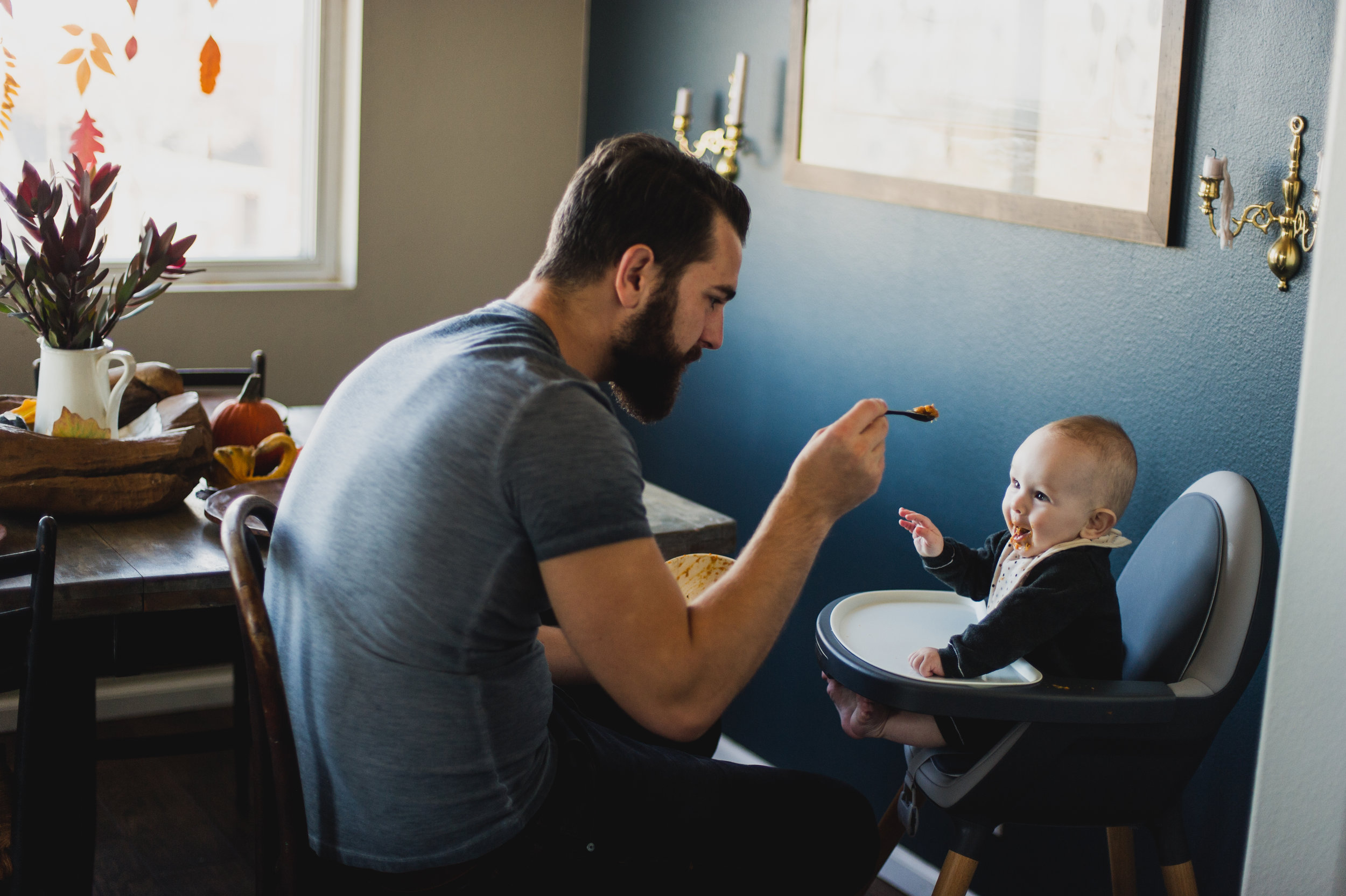 Father feeding child in highchair