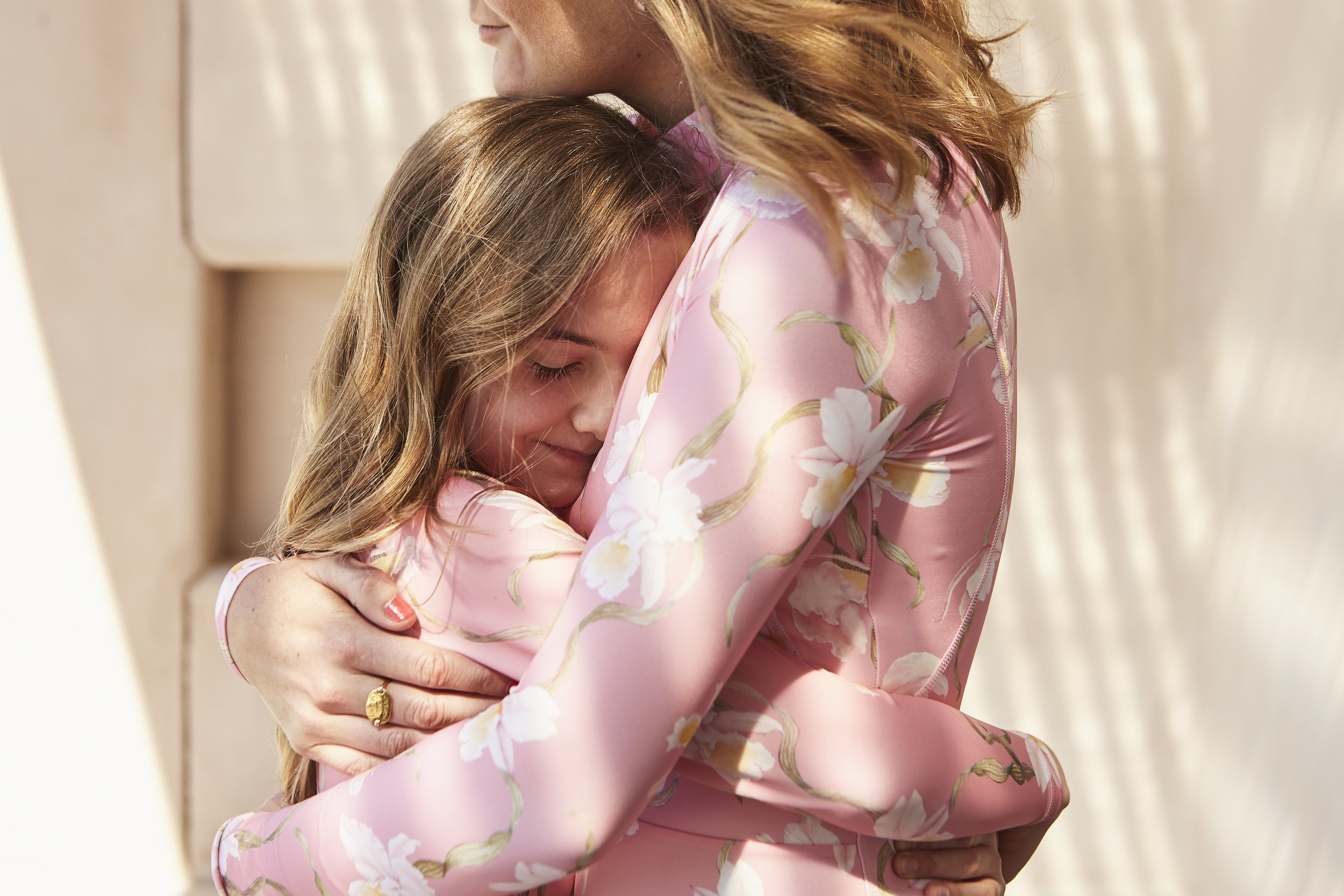 Heather wears the Original Sexie Rashie in Chic Botanical Pink, and Ava wears the matching Original Girls Rashie.