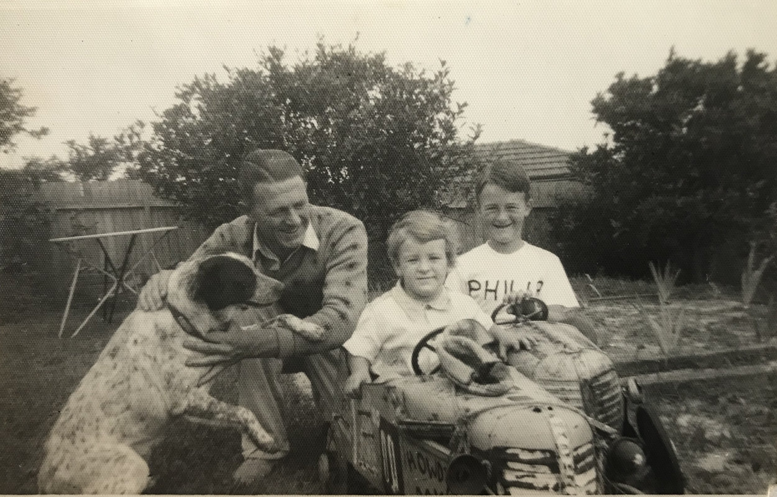 Monty the dog, with Cecil Coster and his children, in the back garden.